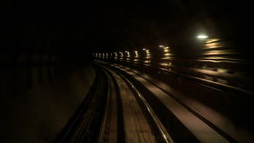 Camera Moves Backward along Metro Rails in Dark Tunnel. Camera moves backward along KL Metro rails through dark tunnel with row of electrical lights stock footage