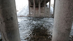Camera moves from the bottom up and removes the river flowing under the bridge in the early spring. stock video