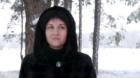 The camera moves close up around the woman. A brunette girl in a black coat stands in a forest or park on a winter snowy stock video
