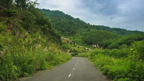 Camera moves fast along road past green hills fields of country stock video footage