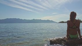 Camera Moves from Girl Sitting on Rock in Ocean to Hilly Beach. Camera moves from slim girl in bikini on small rock in shallow ocean to pictorial tropical hilly stock video