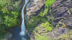 Camera moves from lake along high waterfall tagu in jungle. Drone camera moves from blue lake along high waterfall Tagu stream running between cliffs and stock video footage