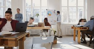 Camera moves left along modern loft office, happy multiethnic business people enjoy working at healthy trendy workplace. Positive relaxed corporate managers in stock footage
