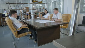 Camera Moves Past Shelves along Room with Manager Meeting. KAZAN, TATARSTAN/RUSSIA - MAY 11 2016: Camera moves past stylish metal shelves along room with manager stock video footage