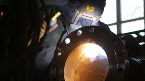 Camera moves past worker welding pipe part in gas enterprise stock video