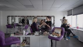 The camera moves in a spacious room where makeup artists hold master class for their permanent and wealthy clients stock video footage