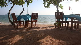 Camera moves between tables served at sand beach. Camera moves between two restaurant tables with waving clothes served at sand beach against sea and boats stock footage