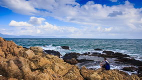 Camera Moves to Backpack Tourist Sitting on Rocky Beach stock video