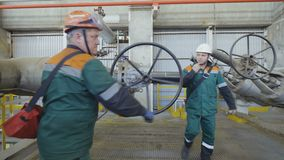 Camera Moves to Employee Turning Round Large Lever. KAZAN, TATARSTAN/RUSSIA - SEPTEMBER 19 2017: Camera moves to employee in green uniform turning round large stock video footage