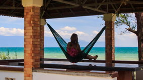 Camera Moves to Girl in Hammock in Red Roof Pavilion on Beach stock video footage