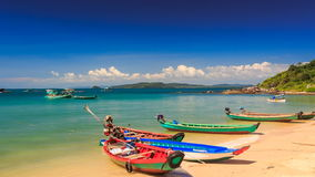 Camera Moves to Tourist Boats at Beach against Island in Vietnam. Camera moves to Vietnamese tourist boats standing half on golden sand beach against green hills stock video