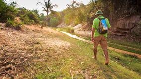 Camera Moves to Tourist Walking along Narrow Fairy Stream stock footage