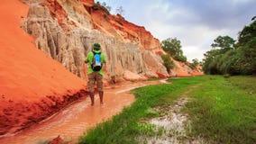Camera Moves to Tourist Walking along Narrow Fairy Stream stock video