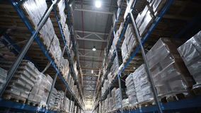 Camera moves up on shelves of cardboard boxes inside a storage warehouse stock footage