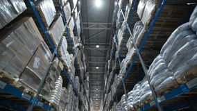 Camera moves up on shelves of cardboard boxes inside a storage warehouse stock video