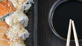 Camera moves up. Stylishly laid sushi set on a black wooden background next to soy sauce and Chinese bamboo sticks. Camera moves up. Stylishly laid sushi set on stock video