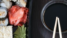 Camera moves up. Stylishly laid sushi set on a black wooden background next to soy sauce and Chinese bamboo sticks. Camera moves up. Stylishly laid sushi set on stock video footage