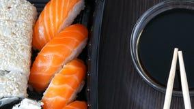Camera moves up. Stylishly laid sushi set on a black wooden background next to soy sauce and Chinese bamboo sticks. Camera moves up. Stylishly laid sushi set on stock footage