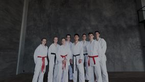 The camera moves and zoom in to a group of young fighters while they are standing together barefoot and looking at the. Camera. Gallant, bold and focused teens stock video footage