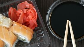 Camera moves zooms. Stylishly laid sushi set on a black wooden background next to soy sauce and Chinese bamboo sticks. Camera moves zooms. Stylishly laid sushi stock video footage