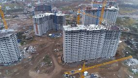A camera moving away from unfinished apartment buildings. A camera zooming out from unfinished apartment block during construction stock video