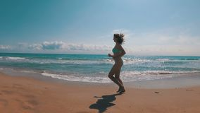 The Camera is Moving behind the Woman Running along the sea Beach in Slow Motion. The Camera is Moving behind the Woman Running along the sea Beach. Slow Motion stock video