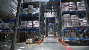 Camera moving between palettes with ordered goods and materials at warehouse. Large warehouse logistics terminal. Multi level storage with racks full of goods stock footage