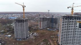 A camera moving between several unfinished apartment buildings. A camera moving between rows of unfinished apartment buildings and tower cranes stock video footage