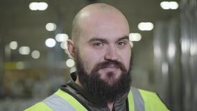 Camera moving up, portrait of bearded baldheaded Caucasian man smiling at camera. Happy worker in green vest standing at