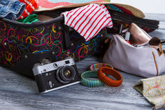 Camera near suitcase with clothes. Colorful striped bracelets. Vintage camera on gray shelf. Take some pictures during journey Stock Photo