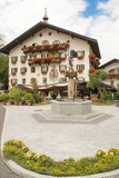Camera nel Tirolo con il pozzo d'acqua e bei fiori sul balcone Fotografia Stock Libera da Diritti