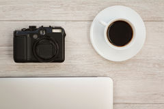 Camera next to a cup of coffee and a laptop Stock Image
