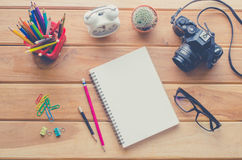 Camera, notebook,pencil and eyeglasses on wood table. Royalty Free Stock Photos