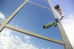 Camera on office building reflecting sky Stock Photos