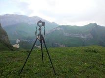 Camera op een driepoot, die mistige bergen schieten stock afbeeldingen