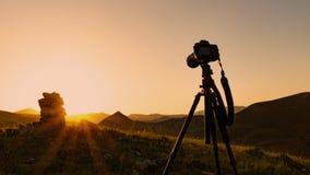 Camera op een driepoot, die een zonsondergang schiet royalty-vrije stock foto's