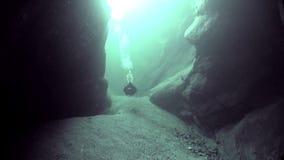 Camera operator in refraction of sunlight underwater in river Verzasca.