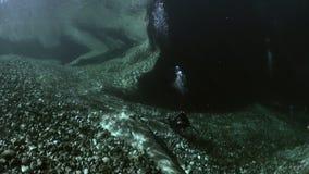 Camera operator in refraction of sunlight underwater in transparent river.