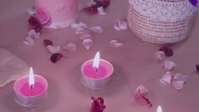 Camera panning on romantic decoration with burning candles and rose petals. Camera panning on romantic decoration, installation on a table. Burning candles and stock video