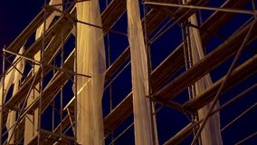 Camera panning on scaffold construction.  Night scene Artificial lighting. Scaffolding. White canvas waving blown by the wind stock footage