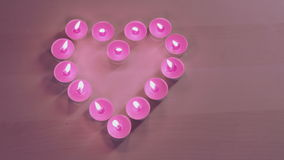 Camera pans through burning candles placed in heart shape. From left to right stock video