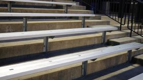 Camera pans over empty bleachers at a sporting event at night.  stock video
