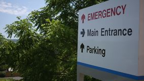 Camera pans to hospital directional sign near small town medical unit. June 21 2018 stock footage