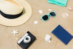 Camera, passport, sunglasses and hat on beach sand stock images