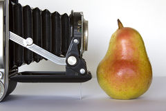 Camera and pear. Royalty Free Stock Image