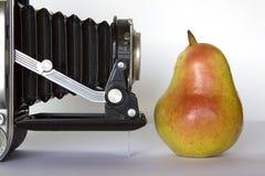 Camera and pear. Royalty Free Stock Image