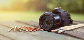 Camera with pencil and brush - banner Stock Photography