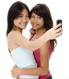 Camera Phone 2. Two cute young women take their picture using a phone Royalty Free Stock Photos