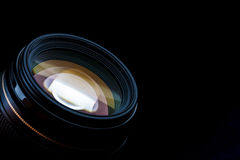 Camera photo lens facing up. Isolated on black background Stock Images
