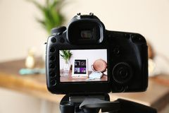 Camera with photo of stylish workplace on screen, selective focus. Fashion blogger. Camera with photo of stylish workplace on screen indoors, selective focus royalty free stock photography